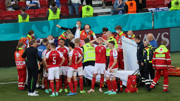 Denmark players protectively surrounded a stricken teammate as medics tried to resuscitate him.