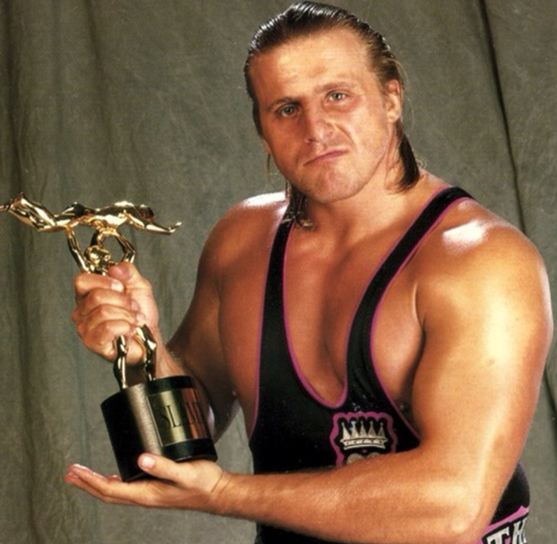 Owen Hart Holding An Award