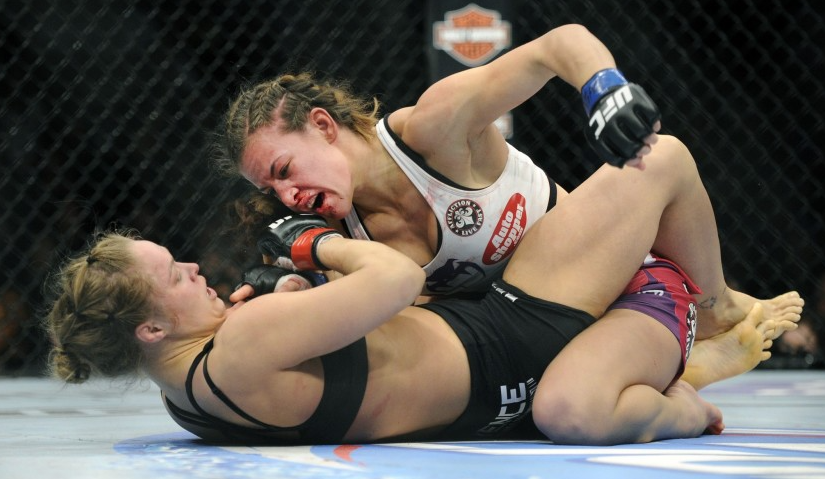 Miesha Tate punches Ronda Rousey during their bantamweight title fight at UFC 168 in Las Vegas
